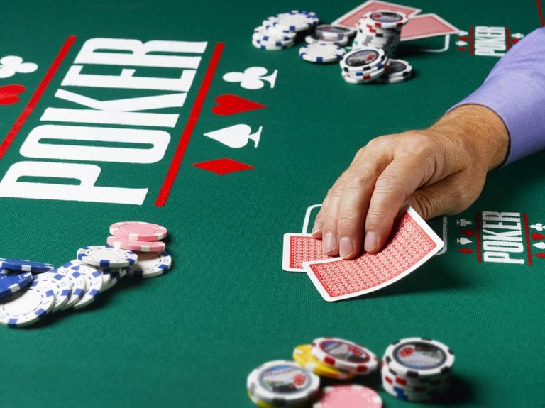 Poker Strategy - Player holding cards in a live game