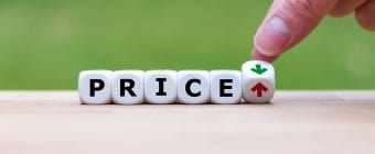 Hand is turning a dice and changes the direction of an arrow symbolizing that the price is going down (or vice versa)